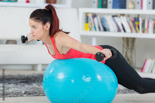 Wall mural young sportswoman doing exercises with ball and dumbbells