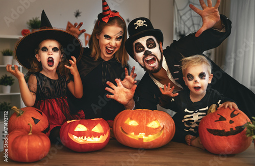 Naklejka happy family mother father and children in costumes and makeup on Halloween.
