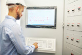 engineer controls technological equipment from remote control board. Scada system for automation equipment - 171495799
