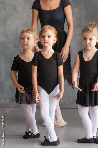 a young woman ballerina in a black dress, white pantyhose and pointe shoes teaches to dance the ballet of young girls ballerinas in black dresses and tights in a dark dance studio © Виталий Сова