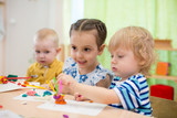 kids doing arts and crafts in day care centre - 171522360
