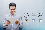 Customer Experience Concept, Happy Businessman holding digital Tablet with a checked box on Excellent Smiley Face Rating for a Satisfaction Survey - 171527748