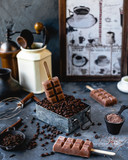 coffee popsicles on wooden sticks with melting popsicle in metal box filled with coffee beans, with cinnamon, cocoa powder, carnations, coffee pot and grinder on gray background - 171541917