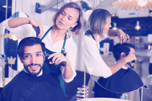 female professional shaving cheerful male's hair