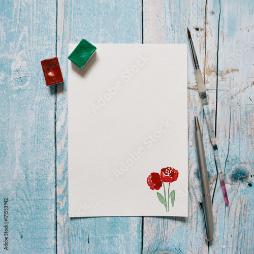 Blank paper with hand painted red roses with copy space on a blue wooden background. Flat lay