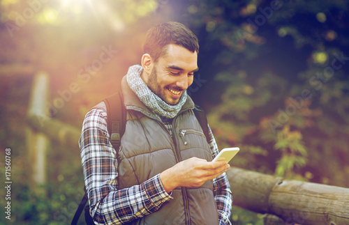 happy man with backpack and smartphone outdoors - 171560768