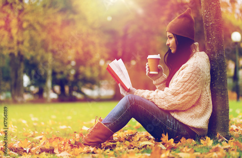 Poster woman with book drinking coffee in autumn park