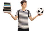 Indecisive teenage student holding football and stack of books - 171575955