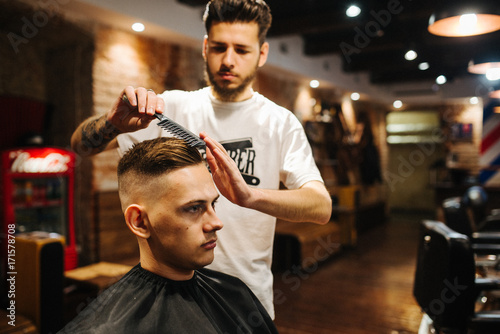 Barber is combing the client's hair comb Poster