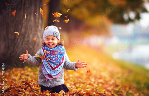 Leinwanddruck Bild adorable happy girl playing with fallen leaves in autumn park
