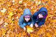 Little girls in autumn orange leaves at park