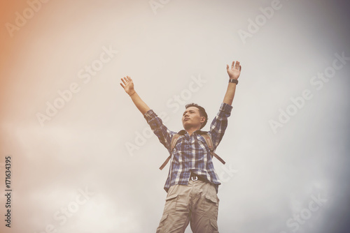 Hiker cheering elated and blissful with arms raised in the sky after hiking Poster