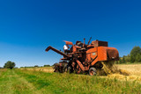Old red combine harvester working in a wheat field. - 171643142