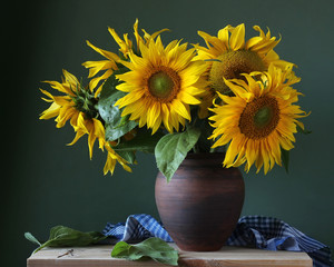 Bouquet of sunflowers in a clay jug.