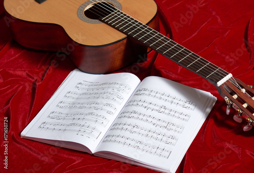 Fotobehang Muziek acoustic guitar and music notes on red velvet fabric, close view of objects