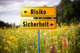 Weggabelung: Entscheidung zwischen Risiko und Sicherheit (Schilder vor Feld mit Wildblumen)