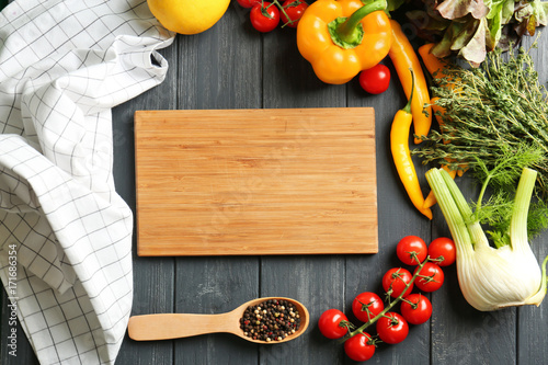 Fotobehang Kruiden 2 Wooden board and vegetables on kitchen table. Cooking classes concept