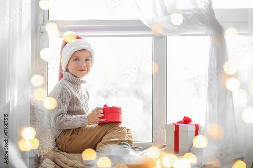 Cute little boy in Santa hat sitting on windowsill at home - 171687515