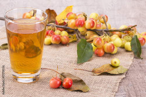 Staande foto Sap glass with apple juice and a branch with small apples on a wooden background.