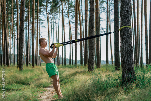 Male athlete excellent training training loops, fresh air in nature summer in park, feel your strength, motivation, full-length. Exercise of the biceps muscles. A sunny day. Stamina of a man. Against