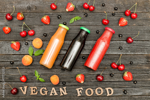 Fotobehang Sap Three bottles with juice, fruit and inscription Vegan Food on a wooden background, food concept