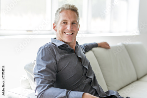 Poster Portrait of single 40s man sitting in sofa