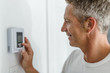 Smiling Man Adjusting Thermostat On Home Heating System