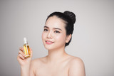 Beauty concept. Asian pretty woman with perfect skin holding oil bottle - 171760311