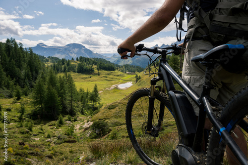 Young adult active man on mountain wearing bike helmet and backpack looking at scenic panorama holding electric bike in sunny summer day outdoor Poster