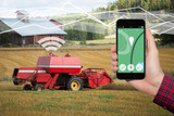 Hand with phone. On the screen control interface of the self driving combine harvester. Internet of things in agriculture - 171778523