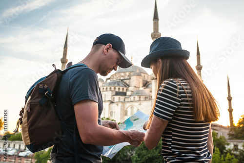 A couple of tourists a young man and a pretty woman look at the map next to the world-famous Blue Mosque also called Sultanahmet in Istanbul, Turkey Poster