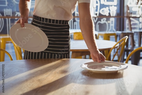 Poster Mid section of waiter arranging plates on table