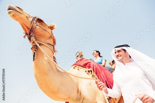 Fotobehang Dubai Arabian Man And Tourist Riding A Camel