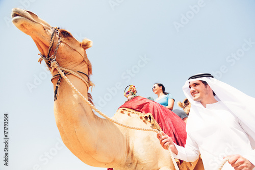 Arabian Man And Tourist Riding A Camel Poster