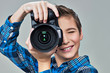 Boy with photo camera looks in the viewfinder