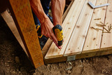 man drilling and measuring wood for deck - 171812547