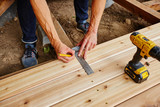 man drilling and measuring wood for deck - 171812548