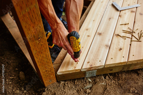 Foto Murales man drilling and measuring wood for deck