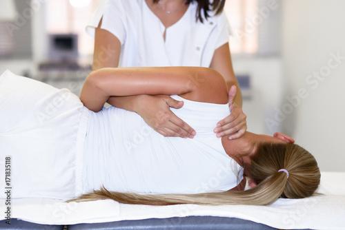 Leinwanddruck Bild Professional female physiotherapist giving shoulder massage to blonde woman
