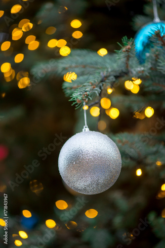 Close-up detail of a glittery Christmas ornament hanging from the branches of a spruce tree, with bokeh lights in the background, Singapore Poster