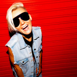 Smile  blonde with short hair in stylish denim clothes and glasses on a red background