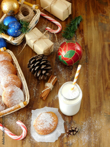 Foto op Aluminium Milkshake Milk in a glass jar with a straw surrounded by Christmas attributes and doughnuts. View from above