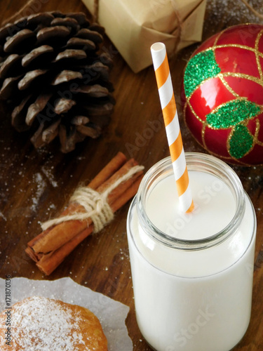 Foto op Aluminium Milkshake Milk in a glass jar with a straw. Christmas attributes in the background. View from above