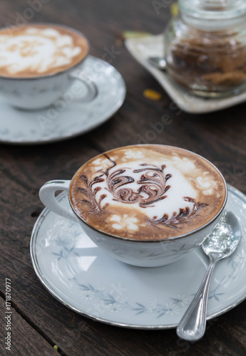 hot coffee with milk cream on wood table Poster