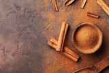 Heap of cinnamon sticks and powder on brown rustic background top view. Aromatic spices. - 171876112