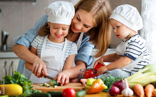Healthy eating. Happy family mother and children  prepares   vegetable salad in kitchen. - 171881748