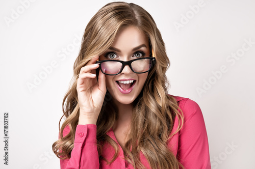 Business woman or student   in  glasses . Beautiful girl in glasses happy and surprised shouts looking forward in glasses . Presenting your product. Expressive facial expressions .