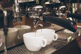 Espresso coffee maker pouring coffee into a cups - 171884121