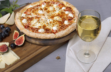 Pizza on board, cheese, bread and glass of wine