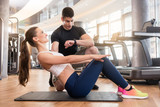 Junge Frau beim Fitness Training im Gym mit Lehrer macht Core Übungen - 171889179